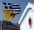 Symi - the twin symbols of Greece, the Naitional flag and the flag of the Greek Orthodox Church, fly proudly in the stiff breeze at Agios Georgios Drakondiotis on the path from Nimborio to Yialos